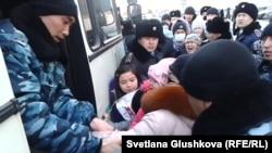 Тұрғын үй проблемасына байланысты наразылық танытқан адамдарды балаларымен бірге полиция көлігіне тиеп жатыр. Астана, 6 наурыз 2014 жыл.
