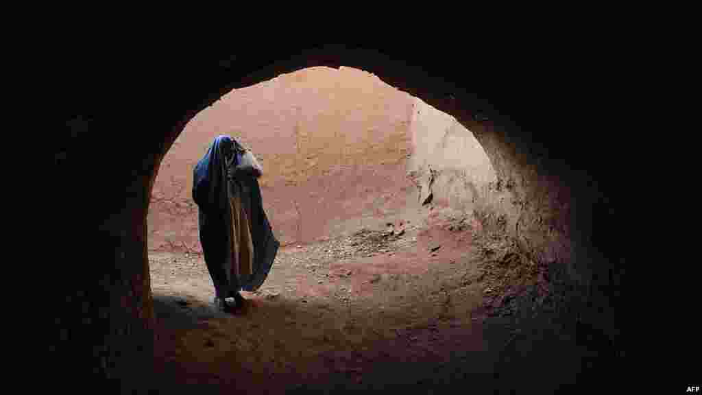 A burqa-clad woman walks in a passageway in the old part of Herat, Afghanistan, on April 23. (AFP/Aref Karimi)