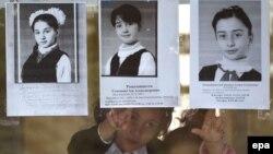 Бесландағы терактіде қаза тапқан оқушы қыздардың суретін көрсетіп тұрған балалар.