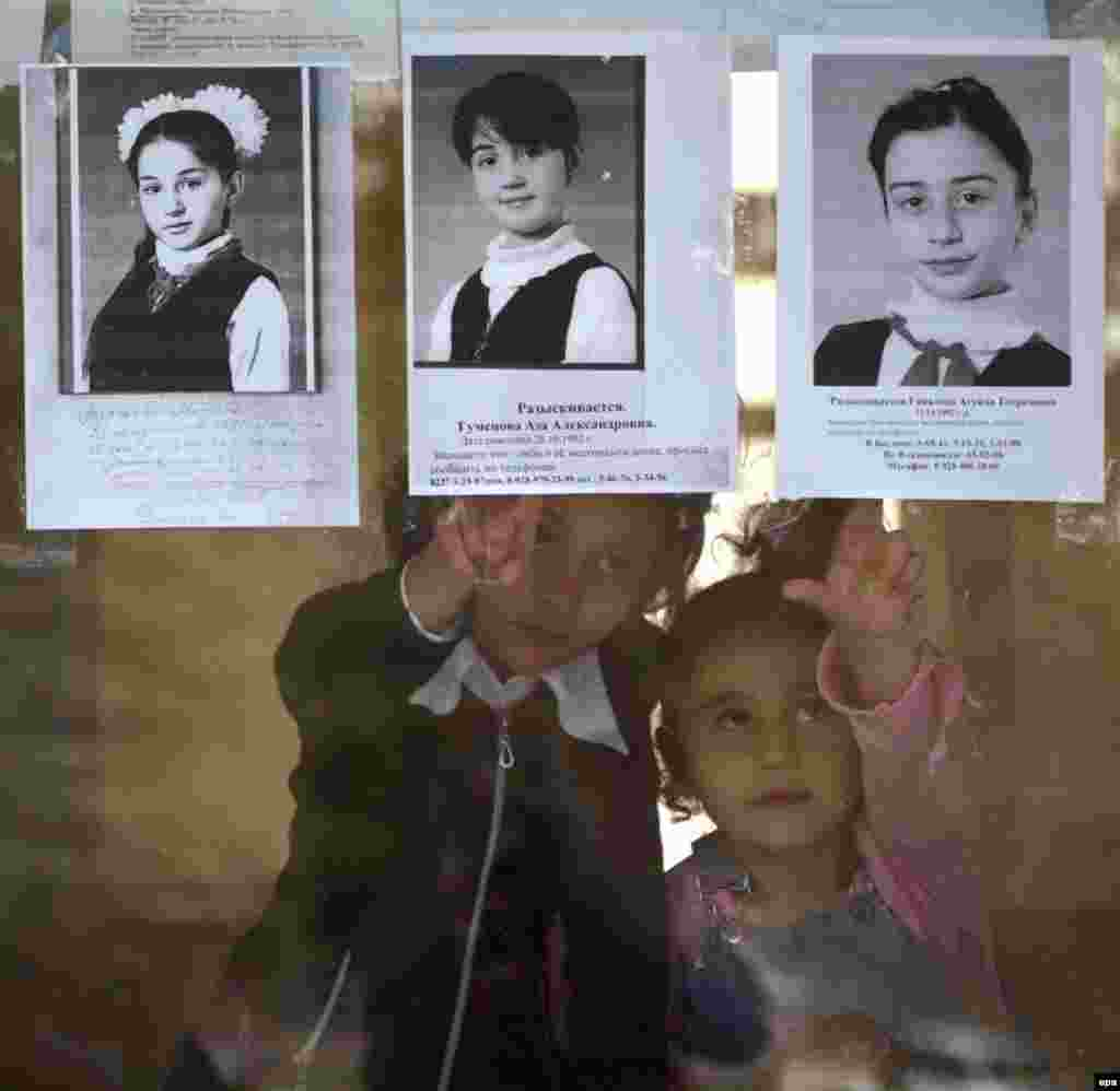 Two girls touch pictures of hostages who remained missing three days after the end of the hostage crisis.