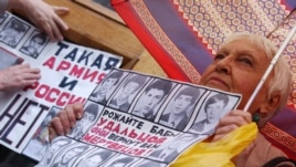 A woman holds a placard with victims of hazing during a protest against conscription in Moscow in 2006