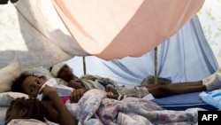 Wouded people lie in a makeshift shelter in the parking lot of the general hospital in Port-au-Prince on January 14.