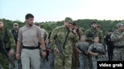 A screengrab from a video posted on Ramzan Kadyrov's VKontakte account of snap defensive drills and inspections that the Chechen strongman ordered, apparently with a view to illustrating the Caucasus republic's defensive readiness.It also shows Kadyrov (center) with a group of armed children dressed in fatigues.