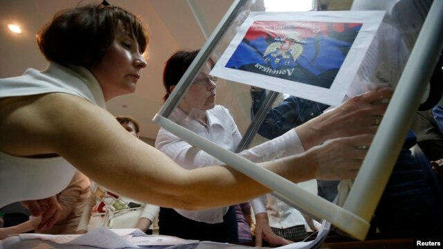 Members of a local separatist election commission empty a ballot box as they start counting votes of the referendum on the status of Donetsk region in Donetsk on May 11.