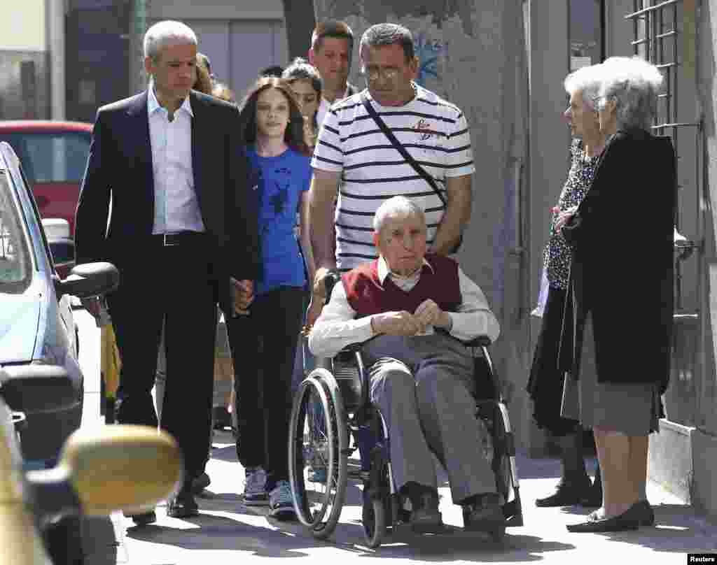 Tadic (left) was accompanied to a downtown-Belgrade polling station on May 20 by daughter Vanja and father Ljuba Tadic (in wheelchair). (REUTERS/Ivan Milutinovic)
