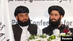 Muhammad Naeem (right), a spokesman for the Office of the Taliban of Afghanistan, speaks during the opening of the Taliban Afghanistan Political Office in Doha on June 18.
