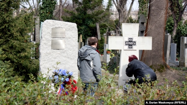 The now-removed plaque (left) is seen on March 18 next to a memorial in Prague's Olsany Cemetery that honors White Army veteran emigres who were defeated by the Bolshevik Red Army.