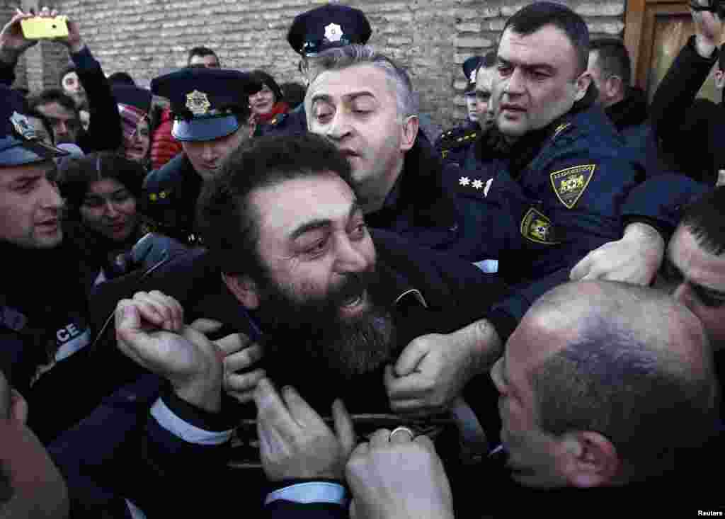 "Police detain an Orthodox activist in front of the Georgian Patriarchate in Tbilisi, where clashes erupted over Patriarch Ilia II's suggestion in his Christmas address that children born to surrogate mothers or through artificial insemination will be ""problematic"" in adulthood. (Reuters/David Mdzinarishvili)"