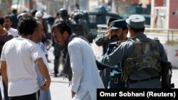 Afghan policemen try to comfort a man whose relatives were stuck at the site of a suicide attack followed by a clash between Afghan forces and insurgents after an attack on a Shi'ite Muslim mosque in Kabul on August 25.