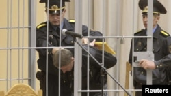 Uladzislau Kavalyou is led into a holding cage before hearings in Minsk on September 15.