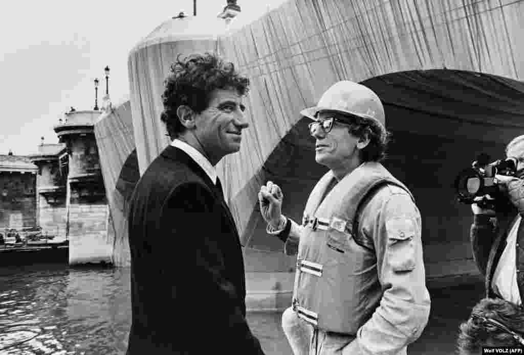 French Culture Minister Jack Lang (left) chats with Christo in Paris on September 18, 1985, during the wrapping of the Pont Neuf.