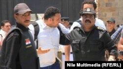 ضابطان من الشرطة المصرية يصطحبان محتجاً في القاهرة