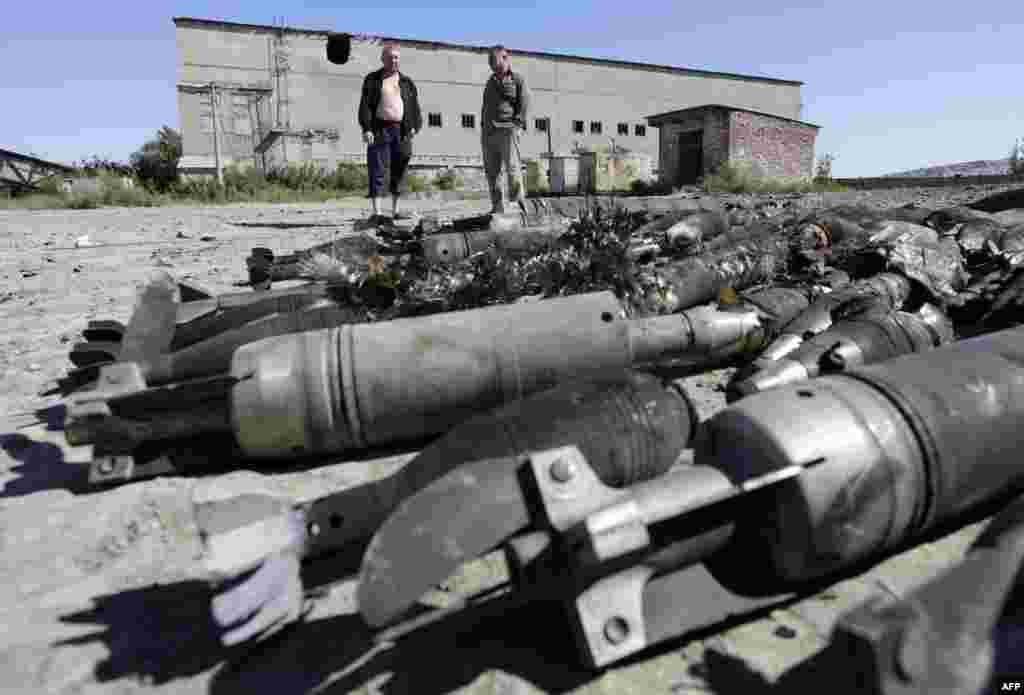 Residents of Kurdyumivka look at an ammunition depot of the Ukrainian armed forces that was destroyed by pro-Russian separatists with Russian Krasnopol guided shells. Two Ukrainian soldiers were killed and 14 more injured over 24 hours in clashes between government forces and pro-Russian rebels in eastern Ukraine, a security official in Kyiv said on August 2. (AFP/Anatolii)