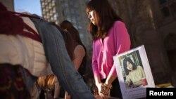 Бостондағы жарылыс құрбандарын еске алуға келгендер терактіден қаза тапқан университет студенті Лу Лингзидің суретіне гүл қойып жатыр. Бостон, АҚШ, сәуір 2013 жыл.
