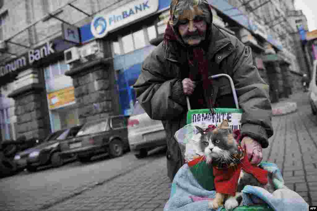 An elderly woman and her cat on a street in central Kyiv on February 24. (AFP/Louisa Gouliamaki)