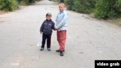 Андрей Кухта (справа) играет с соседом. Село Калачи Акмолинской области, 7 сентября 2014 года.