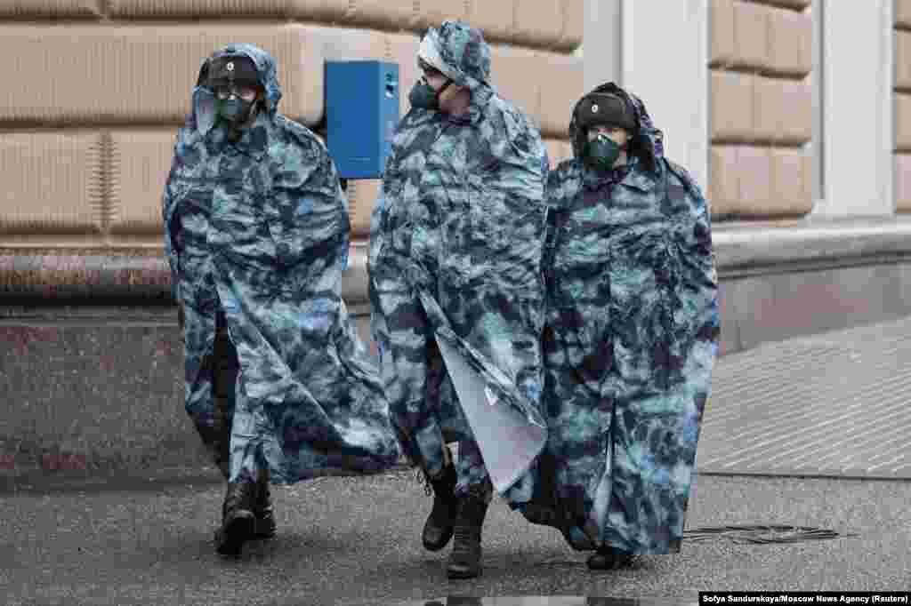 Расейскія праваахоўнікі ў плашчах і ахоўных масках патрулююць вуліцы ў Маскве падчас пандэміі.