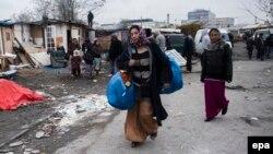 Румынские цыгане покидают нелегальный лагерь, снесенный полицией, в одном из предместий Парижа. Декабрь 2013 года