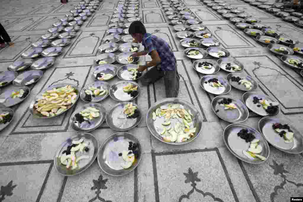 A volunteer prepares plates for the breaking of the fast, known as iftar, during the holy month of Ramadan at a mosque in Karachi, Pakistan. (Reuters/Athar Hussain)