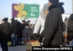 Женщина продает колбасу на автобусной остановке в Астане.