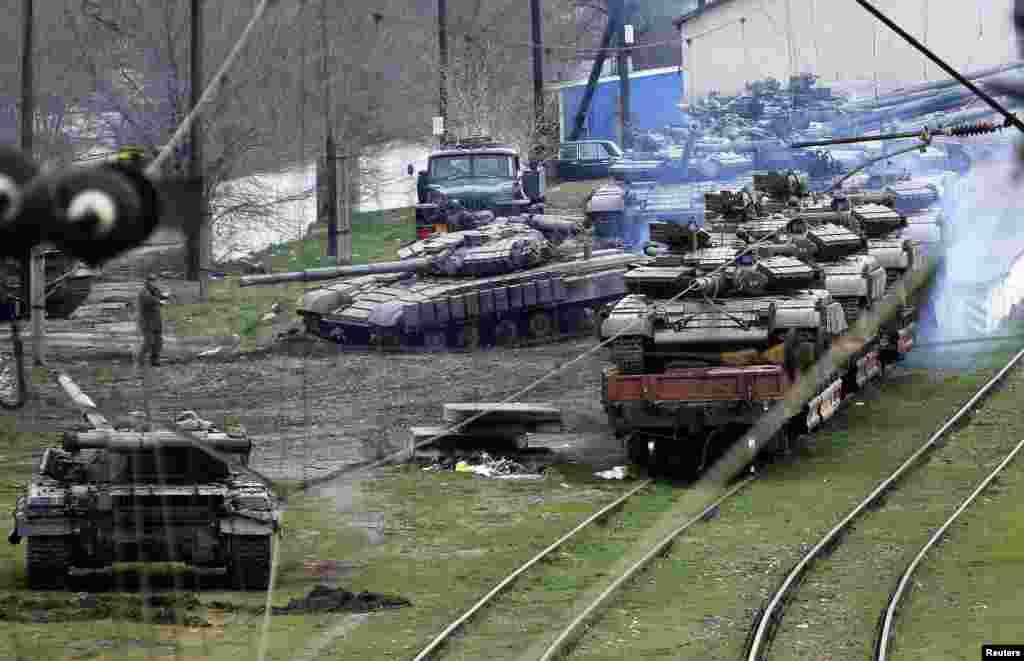 Rusiyeli asker (Perevalnoye k.) A2320 qısımından alınğan ukrain tankını tren platformasına yöñelte, Qırım, mart 27 künü, 2014 senesi