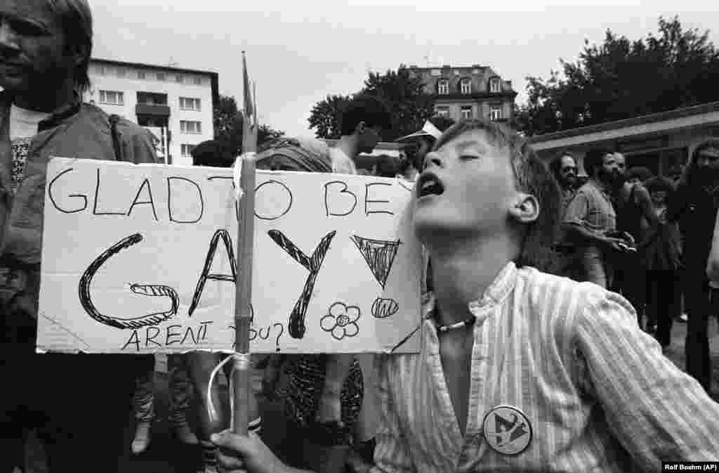 "A 30-year-old Dutch demonstrator displays a sign that reads ""Glad To Be Gay"" during a march in Frankfurt, Germany, on July 28, 1979, which ended a weeklong homosexual meeting. Hundreds of homosexuals converged for a week of movies, theater, rock concerts, and workshops on gay rights. Gays and lesbians from Germany and other countries demanded an end to discrimination against homosexuals."
