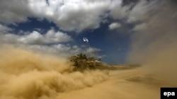 Ushtarët izraelitë e valojnë flamurin gjatë lëvizjes me tankun e tyre në Rripin e Gazës
