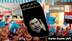 Followers of Shiite cleric Muqtada al-Sadr, seen in the poster, take part in a campaign rally ahead of May 12 parliamentary elections in Tahrir Square, Baghdad, Iraq, Friday, May 4, 2018.