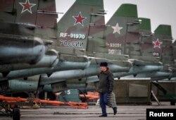 Военнослужащий выполняет учебные действия у истребителей Су-25. Ставропольский край, 12 марта 2015 года.