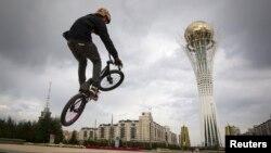 Астанадағы алаңда велосипед теуіп жүрген адам. (Көрнекі сурет)