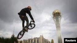 """Велосипедист на фоне монумента """"Байтерек"""", достопримечательности Астаны. Астана, 8 сентября 2013 года."""