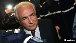 Former IMF head Dominique Strauss-Kahn is escorted by gendarmes while leaving the Paris courts after a hearing in February.