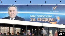 Люди едут в автобусе рядом с баннером с изображением президента Казахстана Нурсултана Назарбаева в Астане. Иллюстративное фото.