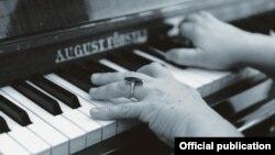 Pianinoda saz çalyp oturan bir aýal