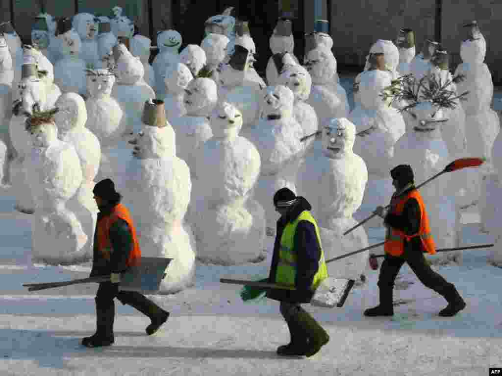 Migrant workers walk past a group of snowmen in Moscow. - Photo by Aleksei Sazonov for AFP