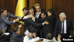 The speaker of the Ukrainian parliament, Volodymyr Lytvyn (right), looks on as deputies scuffle during debate over the draft law on languages.