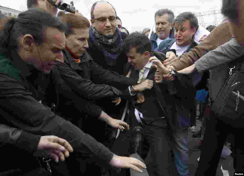 A gay-rights activist (center) scuffles with Orthodox Christian activists.