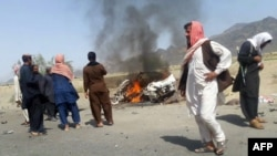 This photograph taken on May 21, 2016 shows Pakistani local residents gathering around a destroyed vehicle hit by a drone strike in which Taliban leader Mullah Akthar Mansur is believed to have been killed.