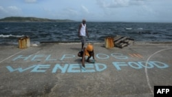 """Filipine - Një njeri shkruan porosi në një fushë basketbolli """"Ndihmë, SOS, kemi nevojë për ushqim"""" (Ilustrim)"""