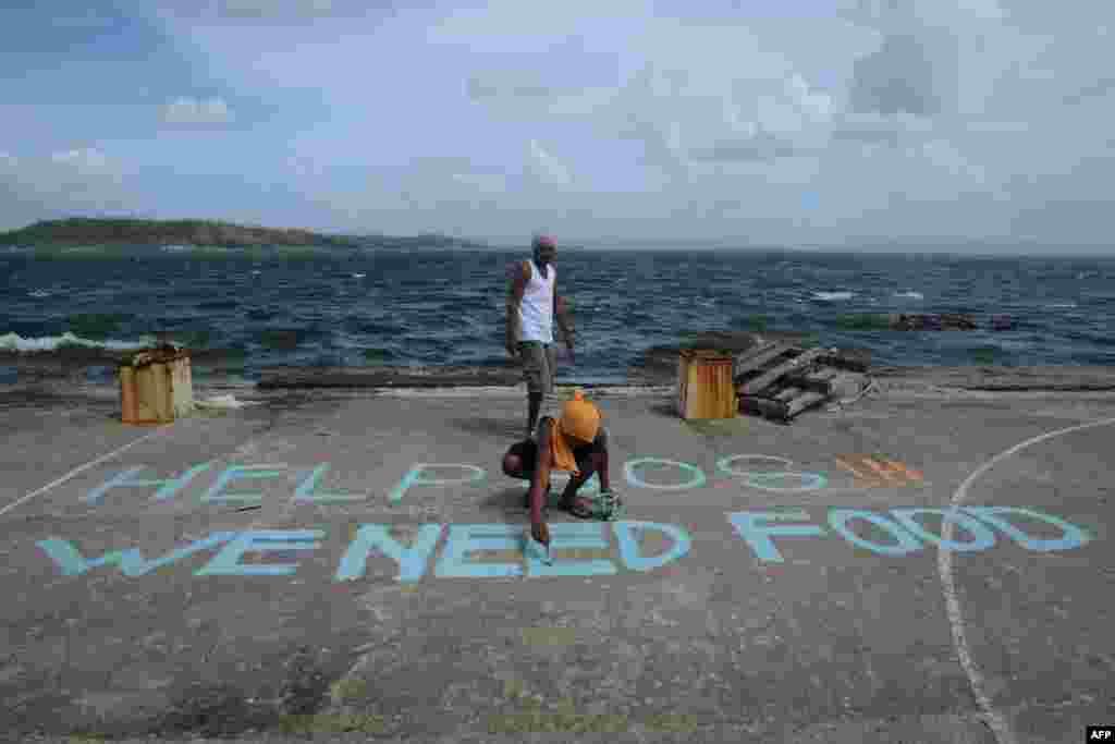 Мужчина пишет обращение с просьбой о помощи на острове Лейте