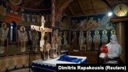Работник во заштитно одело дезинфецира манастир во Грција