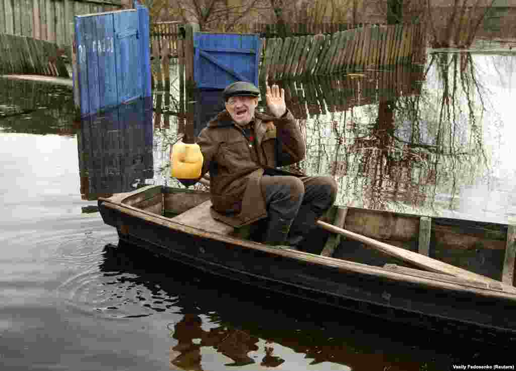 "A pensioner sees the glass half full as he drifts through flooded Khlupin village. A newly released ""Global Emotions"" Gallup poll quizzed 154,000 people in 145 countries. The pollsters found fewer than four in 10 Belarusians recalled feeling positive or negative emotions the previous day."