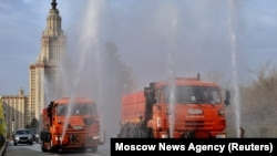 Vehicles spray disinfectant as they sanitize a road near the main building of the Lomonosov Moscow State University in Moscow on April 24.