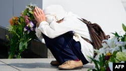 An elderly woman prays for victims of the 1945 atomic bombing of Hiroshima in front of the cenotaph at the Peace Memorial Park in Hiroshima on August 5.