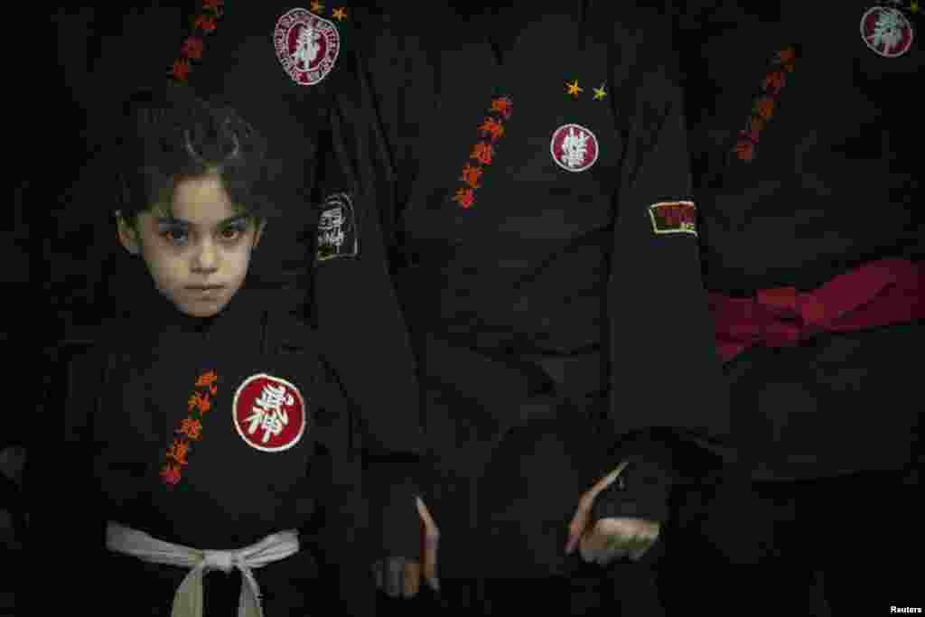 A young ninjutsu practitioner stands beside fellow members of various schools as they wait to showcase their skills to the media in a gym at Karaj.