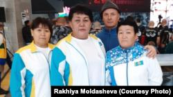Рахия Молдашева (сол жақтан екінші) мен жаттықтырушы Сергей Передистый (оң жақтан екінші) қол күресінен әлем чемпионаты кезінде. Констанца, Румыния, қараша, 2019 жыл.