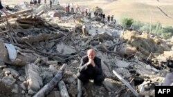 Мужчина сидит на развалинах своего дома. Иран, 12 августа 2012 года.