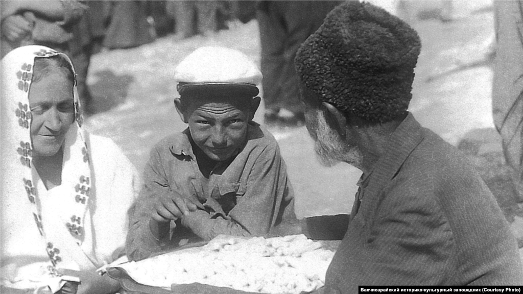 A street vendor in Bakhchysaray during the 1920s. Most artisans sold their own goods in their shops, but every Crimean town also had bustling bazaars. Street vendors would sell necklaces, chains, dresses, and chubuk, which were parts of a smoking pipe.