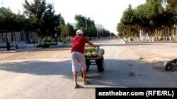Подросток в Туркменистане толкает тележку с дынями и арбузами на продажу. Иллюстративное фото.