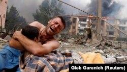 Грузин плачет над телом родственника после бомбежки в Гори, 80 км от Тбилиси. 9 августа, 2008